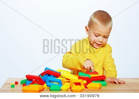 little 3 year old toddler boy playing with bright plastic pyramid blocks over light studio background