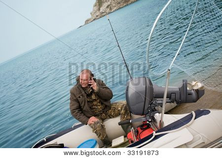 Fisherman was talking on his mobile phone after fishing in the sea.