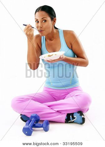 Young latin woman eating cereal after doing exercise.Young woman eating cereal after gym.