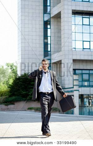 Busy businessman talking on mobile phone while walking