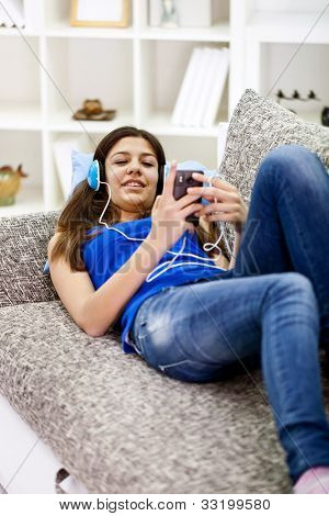 teenager girl lying on sofa and listening music
