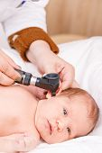 Pediatrician examines two week old babys ear in pediatric clinic. Doctor using otoscope (auriscope) poster