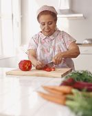 picture of housecoat  - Senior Hispanic woman chopping vegetables - JPG