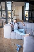 Barefooted Man Chilling On Sofa In The Living Room poster