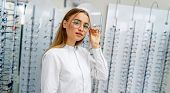 Happy Female Client Or Optician Is Standing With Raw Of Glasses In Background In Optical Shop. Stand poster