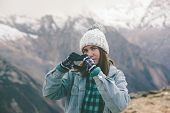 Young traveler girl in gloves and hat standing over snowy mountain peaks and making shape of love he poster