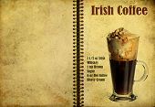 stock photo of frappe  - Oldvintage or grunge Spiral Recipe Notebook with Irish Coffee cocktail on the page - JPG