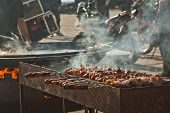 Grilled Meat In A Large Frying Pan. Grilled Vegetables On Motorcycle Festival Background. Blurred Mo poster