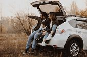 Happy Family Sitting At Open Trunk Of Hatchback Car And Pointing Finger Outdoors. Road Trip Concept. poster
