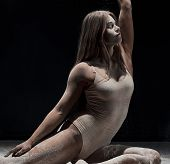 Graceful Girl Posing In White Dust Cloud In Studio poster