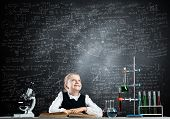 Schoolgirl Sitting At Desk With Open Book. Happy Girl Scientist Studying In Classroom With Chalkboar poster