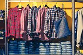 Choice Of Fashion Clothes Of Different Colors On Wooden Hangers. Denim Clothes Are Laid Out In A Clo poster