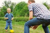 picture of heartwarming  - Father training his little son play in football - JPG
