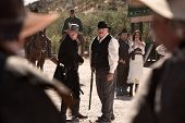 stock photo of gunfights  - Cowboys draw weapons in an old American west gunfight - JPG