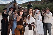 image of gunfights  - Pretty gunfighters lead armed crowd outside in American west town - JPG