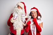 Senior couple wearing Santa Claus costume holding dollars over isolated white background Thinking co poster
