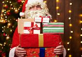 Santa Claus posing with many gifts, sitting indoor near decorated xmas tree with lights - Merry Chri poster