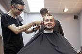 Young Guy Makes A Short Haircut In A Barbershop, A Barber Kazakh Cuts A Man With A Trimmer, Reflecti poster