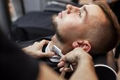 Handsome Guy Cut His Beard With A Razor, Shaving A Short Beard In A Barbershop, Close-up poster