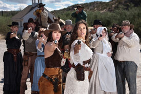 stock photo of gunfights  - Pretty gunfighters lead armed crowd outside in American west town - JPG