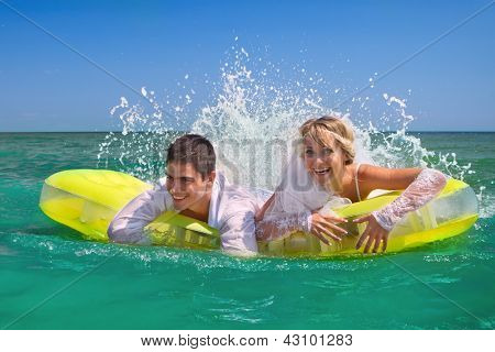 A young and beautiful newly-married couple enjoying on an inflatable mattress has gone mad of pleasure
