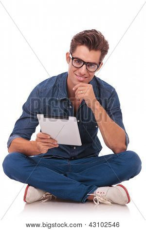 casual young man sitting on the floor with his legs crossed and holding a tablet and rubbing his chin while smiling to the camera. isolated on white