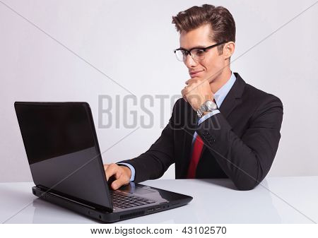 picture of a charming young business man working concentrated at the laptop with a hand on his chin, on gray background