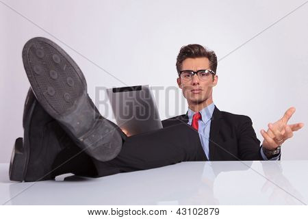 young business man sitting with his legs on the desk and holding a tablet is looking at the camera and questioning you, on gray background