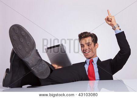 imagens de um jovem homem de negócios sentado com as pernas sobre a mesa e torcendo com seu ponto de dedo