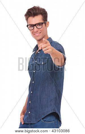 cutout picture of a casual young man pointing and looking at the camera with a hand in his pocket and with a smile on his face. isolated on a white background