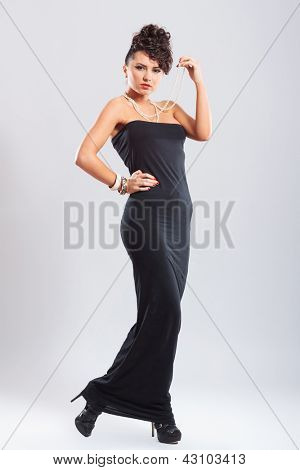 sexy young fashion woman posing with a hand on her hip and holding her pearl necklace with the other while looking at you. on light background