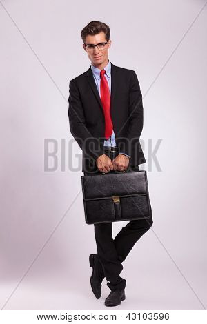 smiling young business man is standing with legs crossed and holding a suitcase with both hands, against gray background