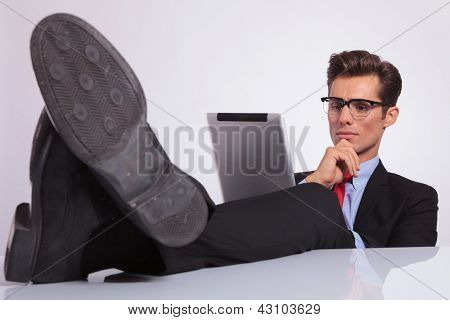 young business man sitting with legs crossed on the desk and looking thoughtfully at his tablet, on gray background