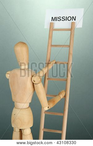 Mannequin on wooden ladder, on grey background