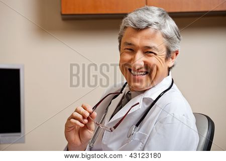 Portrait of a jovial mature male doctor in lab coat holding glasses