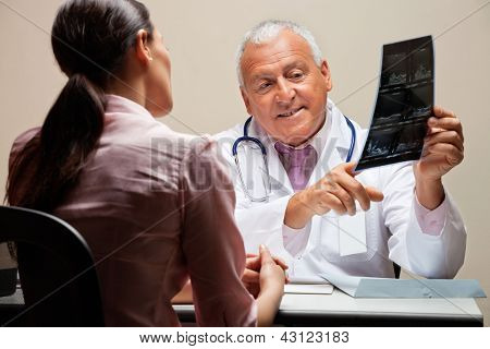 Senior male radiologist explaining x-ray to female patient