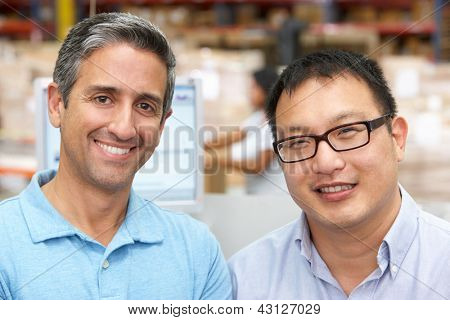 Two Men At Computer Terminal In Distribution Warehouse
