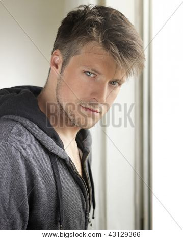 Young good-looking young man near window