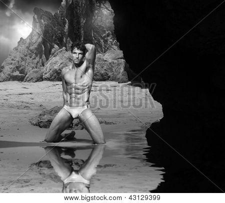 Clássico preto e branco retrato cênico de homem bonito de músculo na praia rochosa