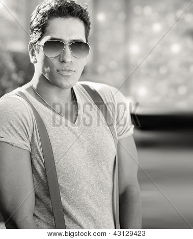 Handsome cool young male model wearing white T-shirt and suspenders with sunglasses