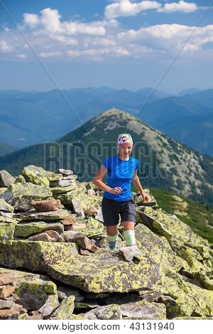 Athlet Looking Girl With Bandage On Knees Jumps Over Stones In Carpathian Mountains