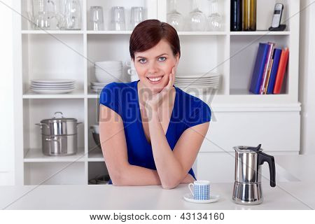 Miling Woman Sitting In Her Kitchen With A Coffee Moka Pot