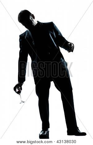 one caucasian man full length silhouette  drunk holding a glass of red wine in studio isolated white background
