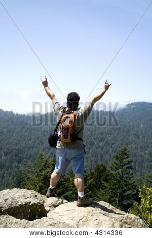 Hiker Shows Sign Of Victory On Top Of Mountain Peak