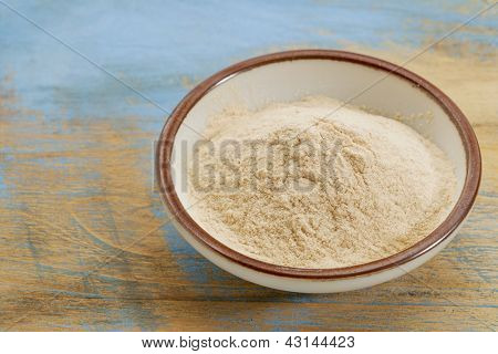 small ceramic bowl of African baobab fruit powder against grunge painted wood background