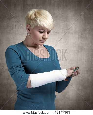 Sad woman looking in  cast on her arm.