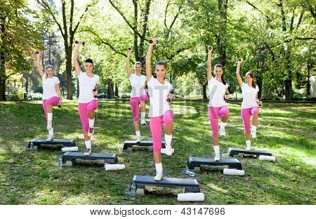 Energetic group of a young women doing fitness exercises outdoor on a sunny day