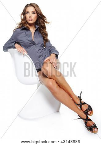Portrait of beautiful young woman sitting on chair isolated over white background