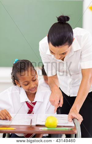 beautiful female primary educator tutoring student in school