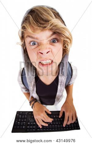 overhead view of angry teen boy playing on computer keyboard